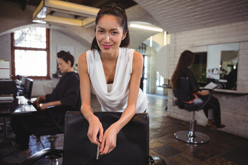 Smiling female hair dresser leaning on chair at salon