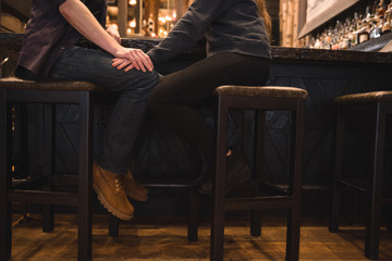Romantic couple sitting on stool at bar counter