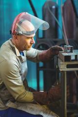 Male welder examining a piece of metal