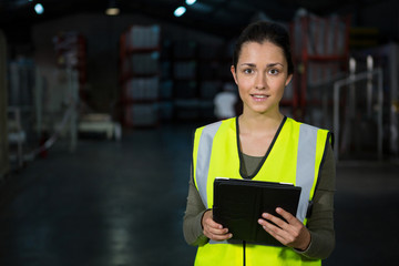 Beautiful young woman using digital tablet in factory