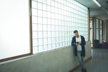 Male executive using mobile phone in corridor