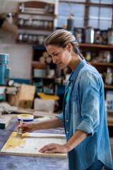 Female carpenter applying varnish on wooden plank