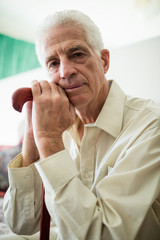 Thoughtful senior man sitting with a cane