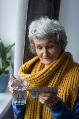 Woman with glass of water holding blister pack