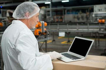 Male worker using laptop in factory