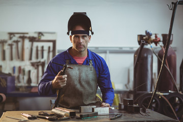 Male welder holding welding torch