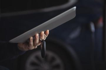 Man holding car key and digital tablet