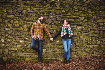 Couple leaning against stone wall