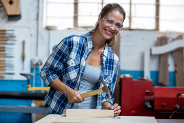 Female carpenter holding a hammer to drive nail into a wooden plank