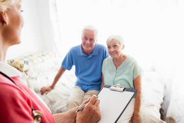 Nurse writing on clipboard and senior couple sitting on a bed
