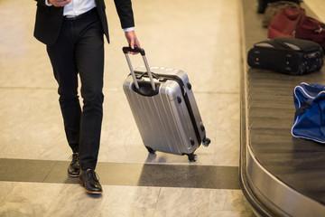 Businessman walking with luggage near baggage claim area