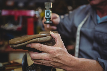 Close up of cobbler hammering on shoe in workshop