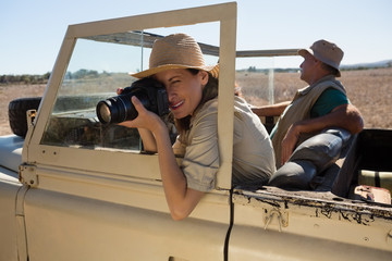 Woman photographing from camera while traveling in off road vehicle on field