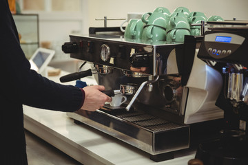 Hand of man holding portafilter under coffee machine