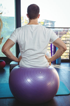 Male patient sitting on exercise ball
