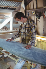 Man making surfboard in workshop