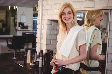 Smiling female hairdresser holding scissor in salon