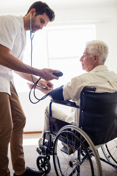 Nurse measuring the blood pressure of a senior man