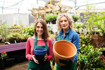 Two female florists holding pot