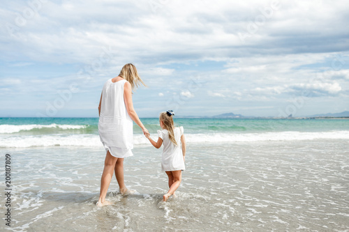 8887e27e9b581 Back view family mother and daughter walking at beach enjoying tropical summer  vacation.
