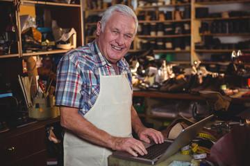 Portrait of shoemaker using laptop