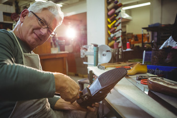 Portrait of shoemaker repairing a shoe