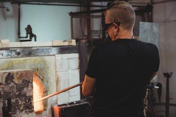 Glassblower heating a glass in furnace