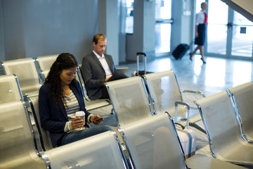Commuter using mobile phone in waiting area