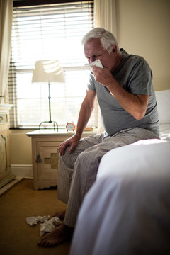 Senior man using a tissue to blow his nose in the bedroom