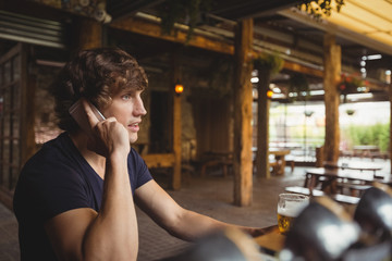 Man talking on mobile phone in bar
