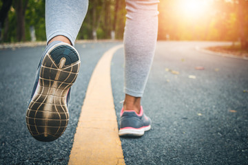 Women runner feet on road in workout wellness concept.