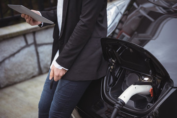 Mid section of woman using digital tablet while charging electric car