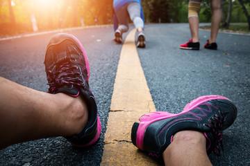 Women and men runner feet on road in workout wellness concept.