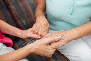 Nurse and senior woman holding hands