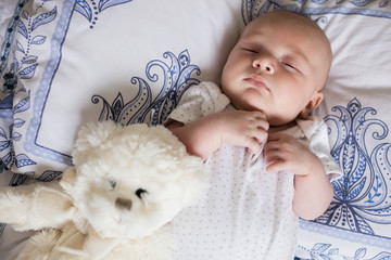 Baby sleeping on bed with soft toy in bedroom