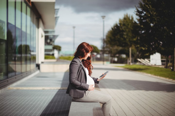 Pregnant businesswoman using digital tablet