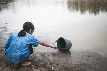 Woman hand are scooping water on cracked ground, Crisis of water shortage.