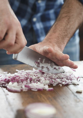 Close up male hands chopped fresh red onion