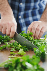 Male hands chopping fresh parsley close up