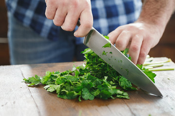 Close up male hands chopping fresh parsley