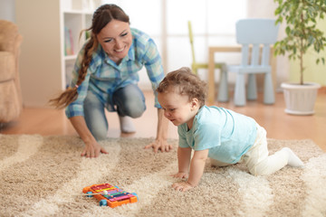 Happy mother looking at her baby son crawling on floor in children room