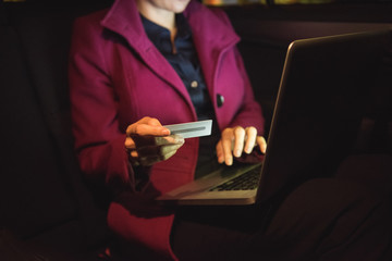 Businesswoman doing online shopping on laptop with credit card