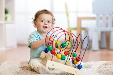 baby child playing with educational toy in nursery
