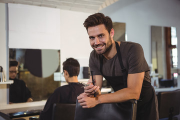 Male hairdresser holding scissor and comb in salon