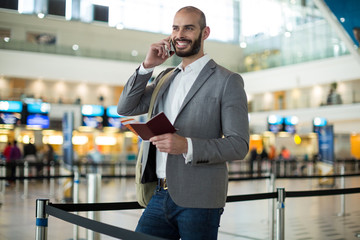 Smiling businessman holding a boarding pass and talking on mobile phone