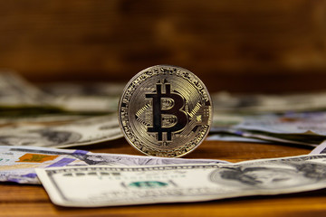 Silver bitcoin and dollars on wooden background