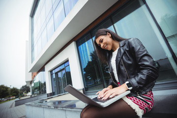 Woman using laptop outside the office building