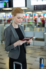 Businesswoman with luggage checking her boarding pass
