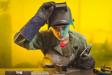 Female welder examining a piece of metal