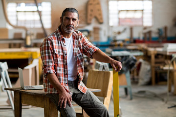 Portrait of mature man sitting on table in workshop